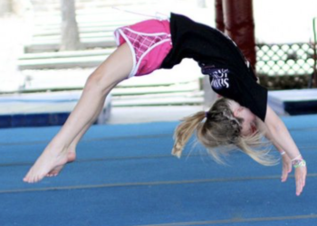 girl doing a back handspring on a gymnastics mat
