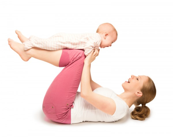 mother on her back balancing her infant on her knees as part of a gymnastics class