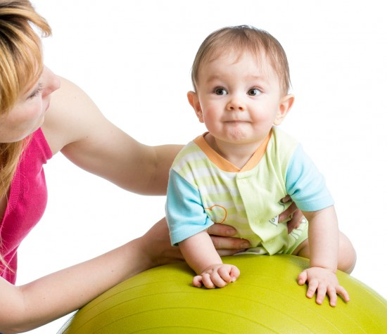 mother helping young child balance on an exercise ball