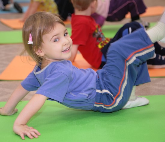 young girl doing exercises on a mat in gymnastics class