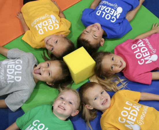 Children lay on a gymnastics mat.