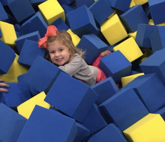 Little girl smiles in foam cube pit.