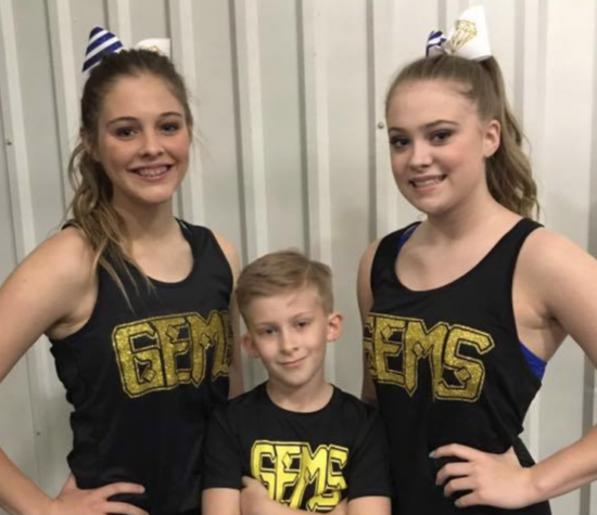 two girls and a boy in cheer team attire smiling at the camera