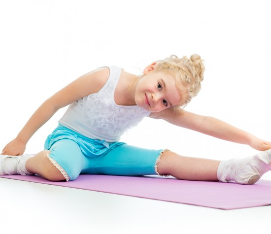 little girl sitting on a mat and stretching