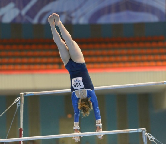 girl in blue leotard on the high bar