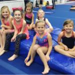 Children gymnasts sit smiling on mats
