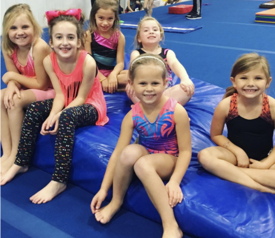 Children gymnasts sit smiling on mats