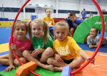 kids sitting on mats in gymnastics class smiling at the camera