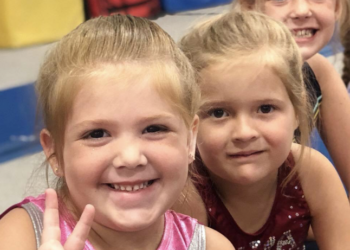 close up of two girls in gymnastics leotards smiling at the camera
