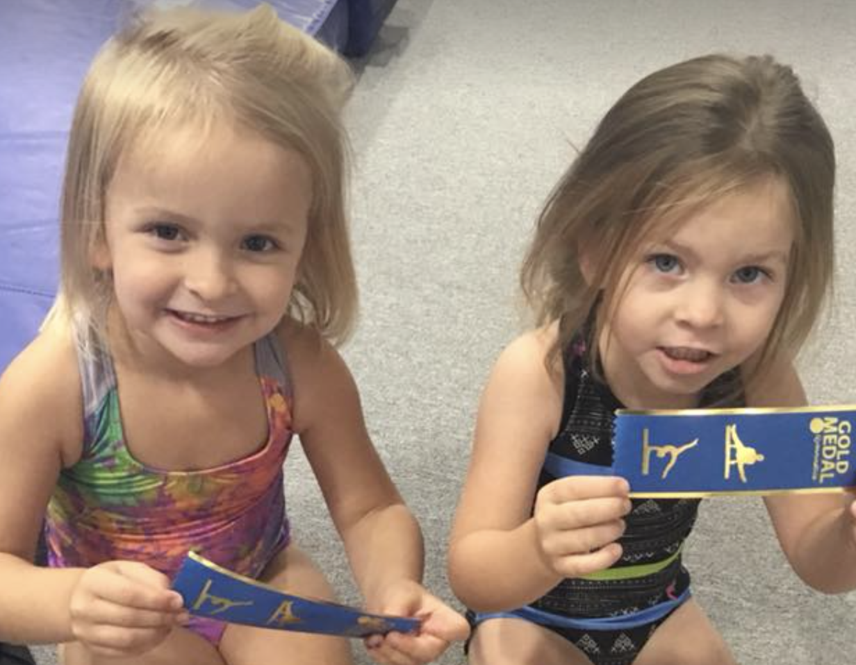 little girls in gymnastics attire smiling at the camera and holding blue ribbons