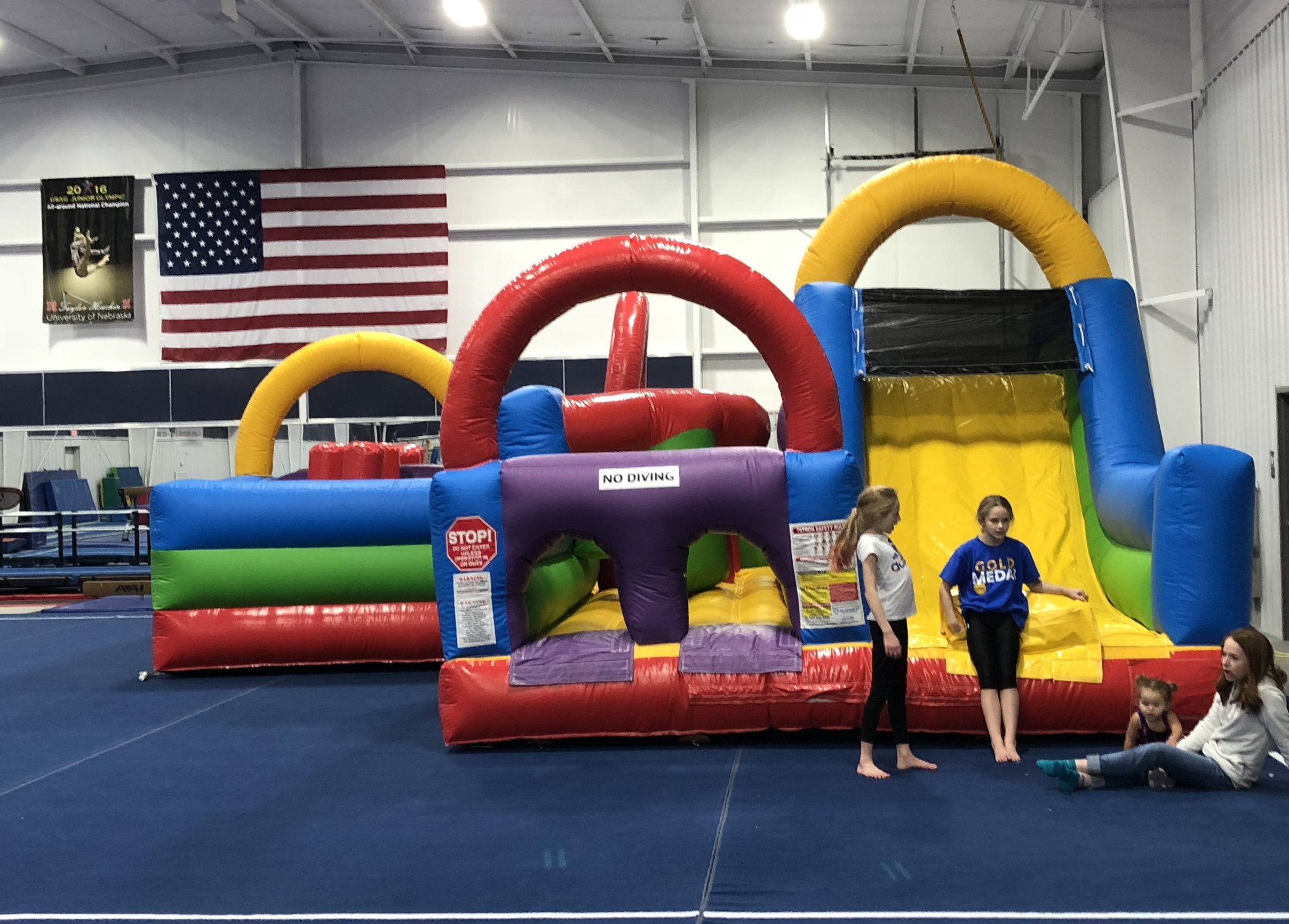 Children play on a bouncy castle in the gym.