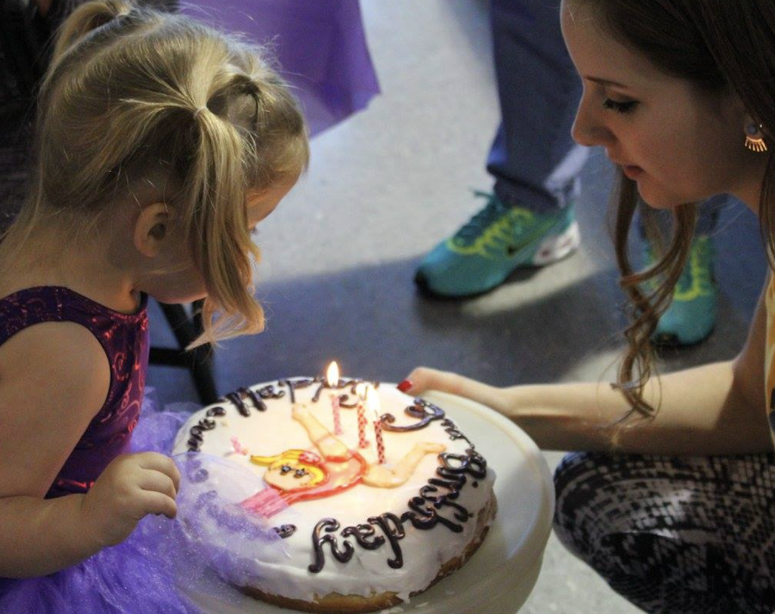 A little girl blows out candles on her birthday cake.