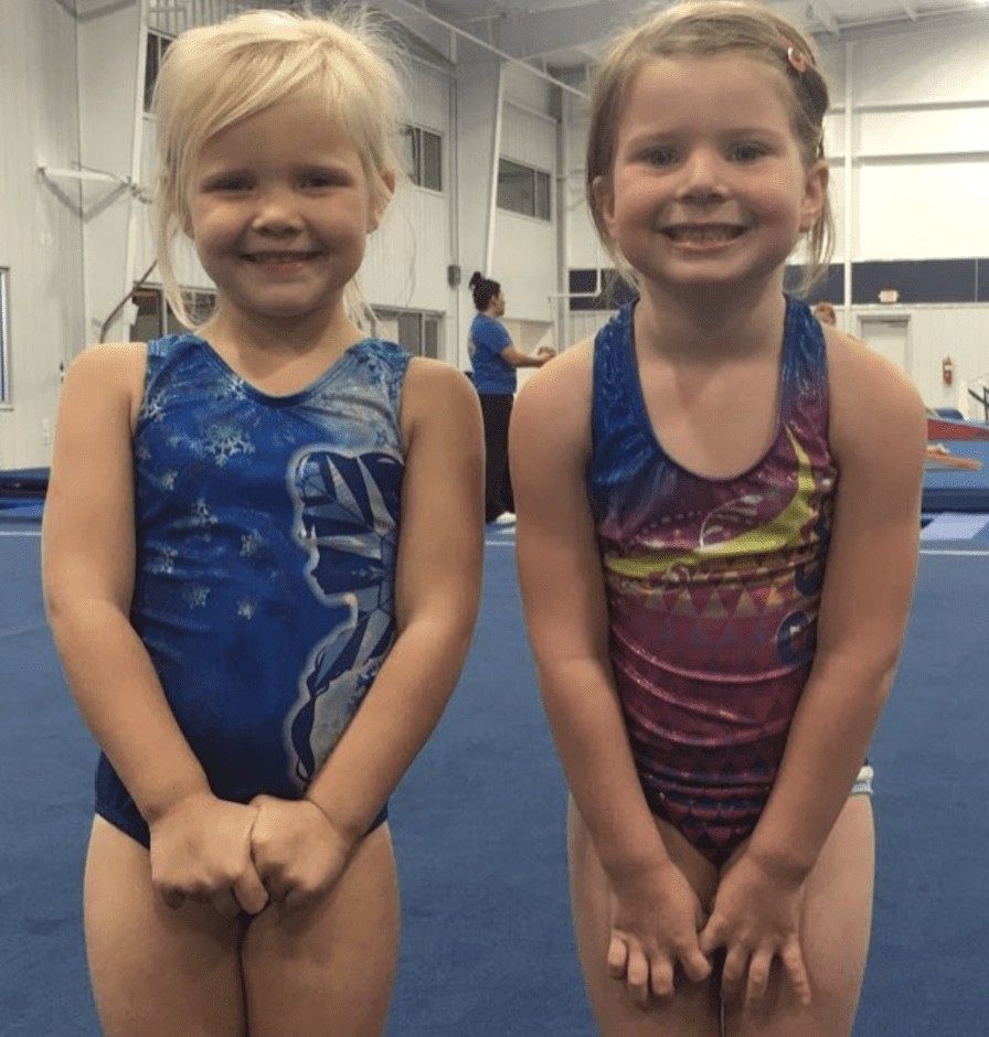 Two little girls in leotards smile.