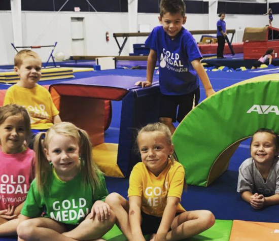 A group of children on gymnastics mats smile.