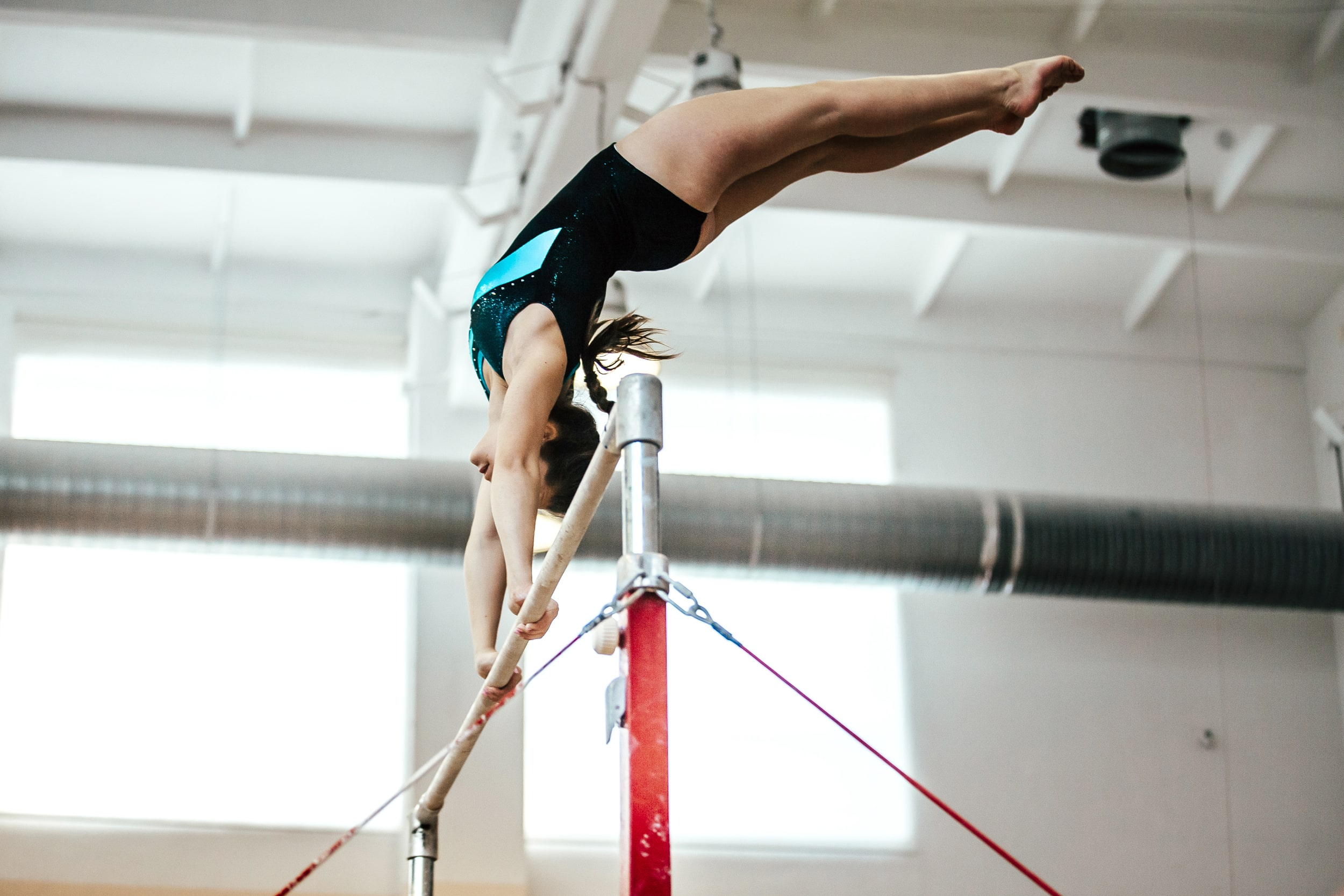 Girl using the high bar in a gymnastics gym