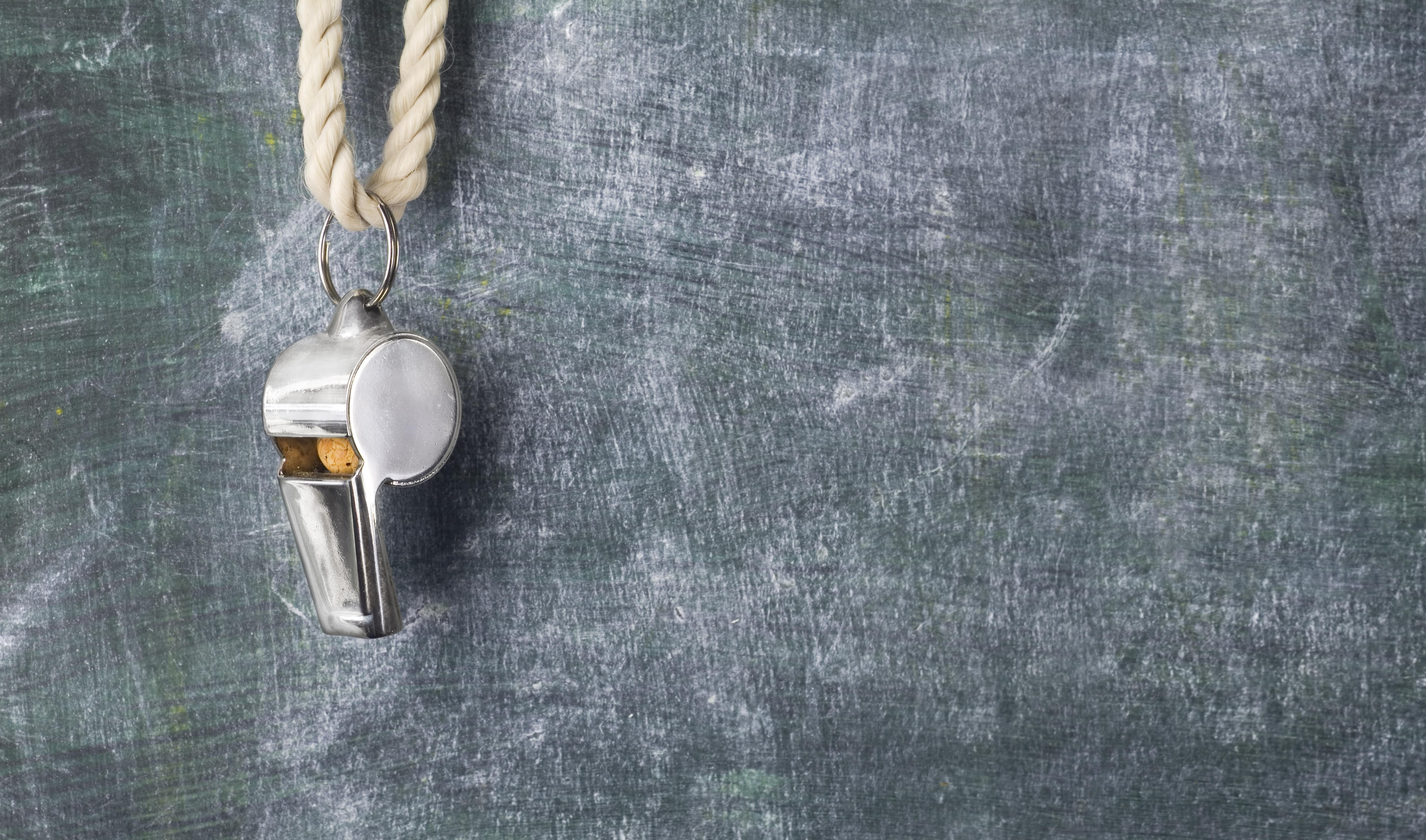 Image of a coach's whistle against a grey concrete background