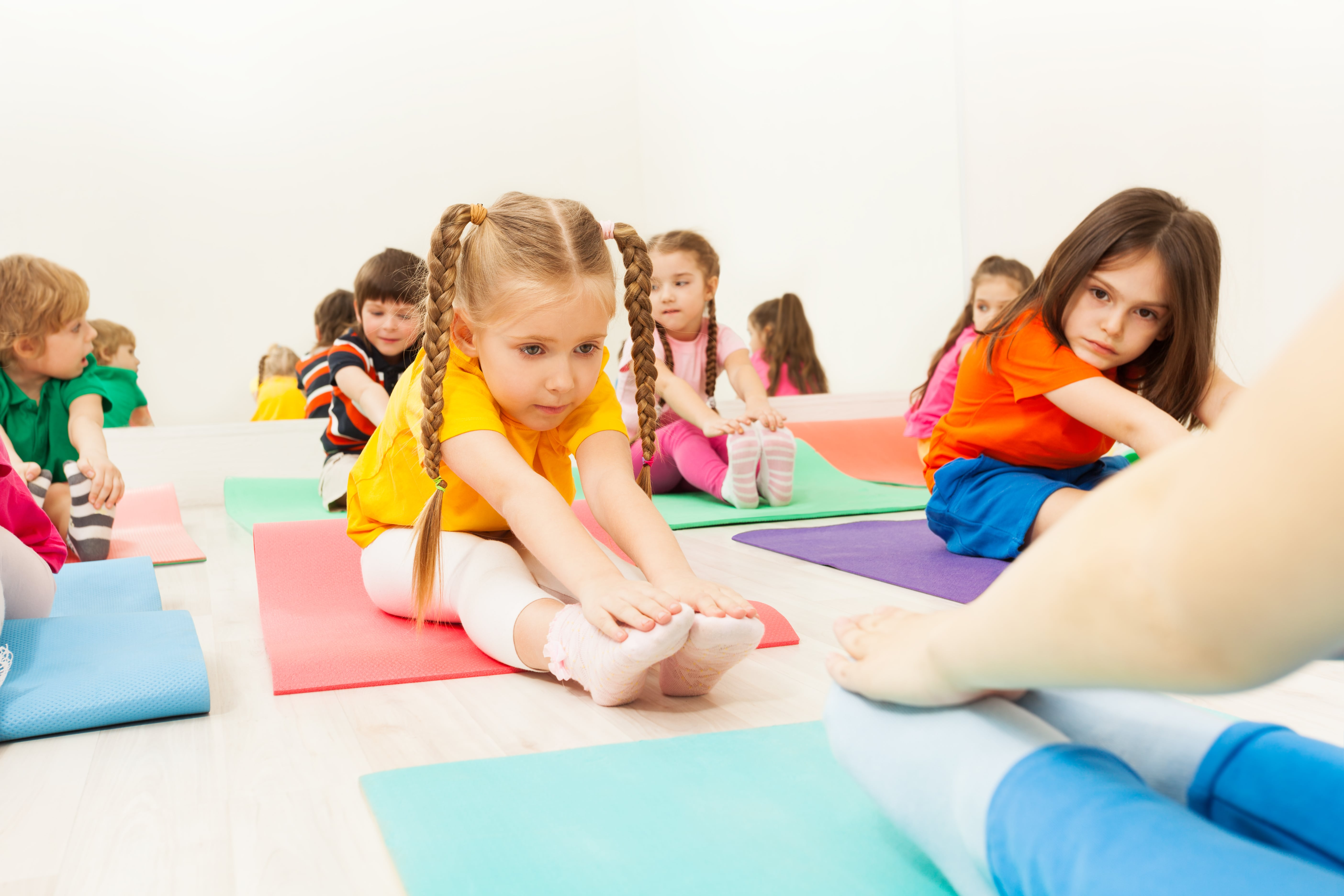 Children on the gym floor doing stretches