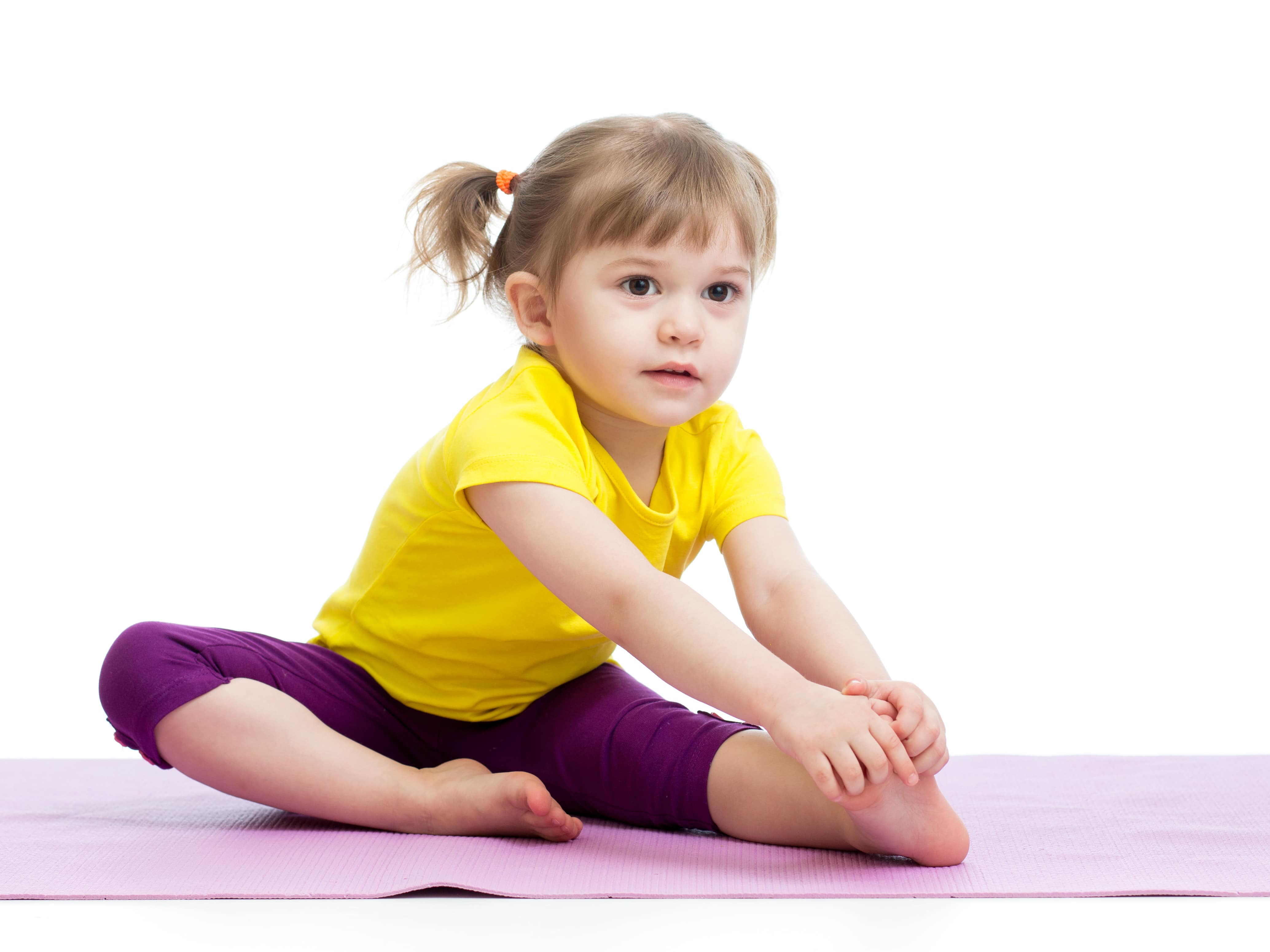 Young girl stretching on a mat