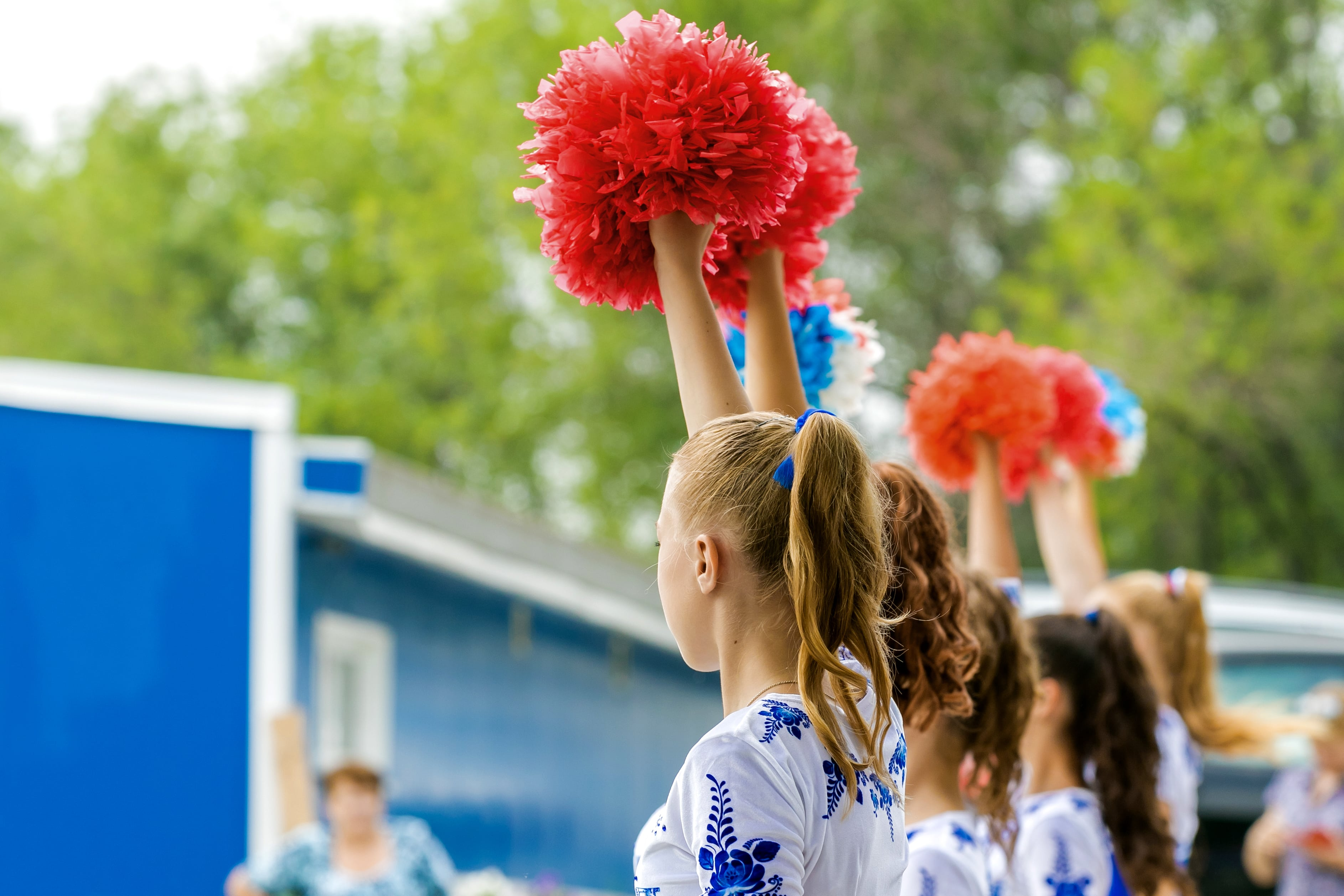 Group of girls holding red pom poms