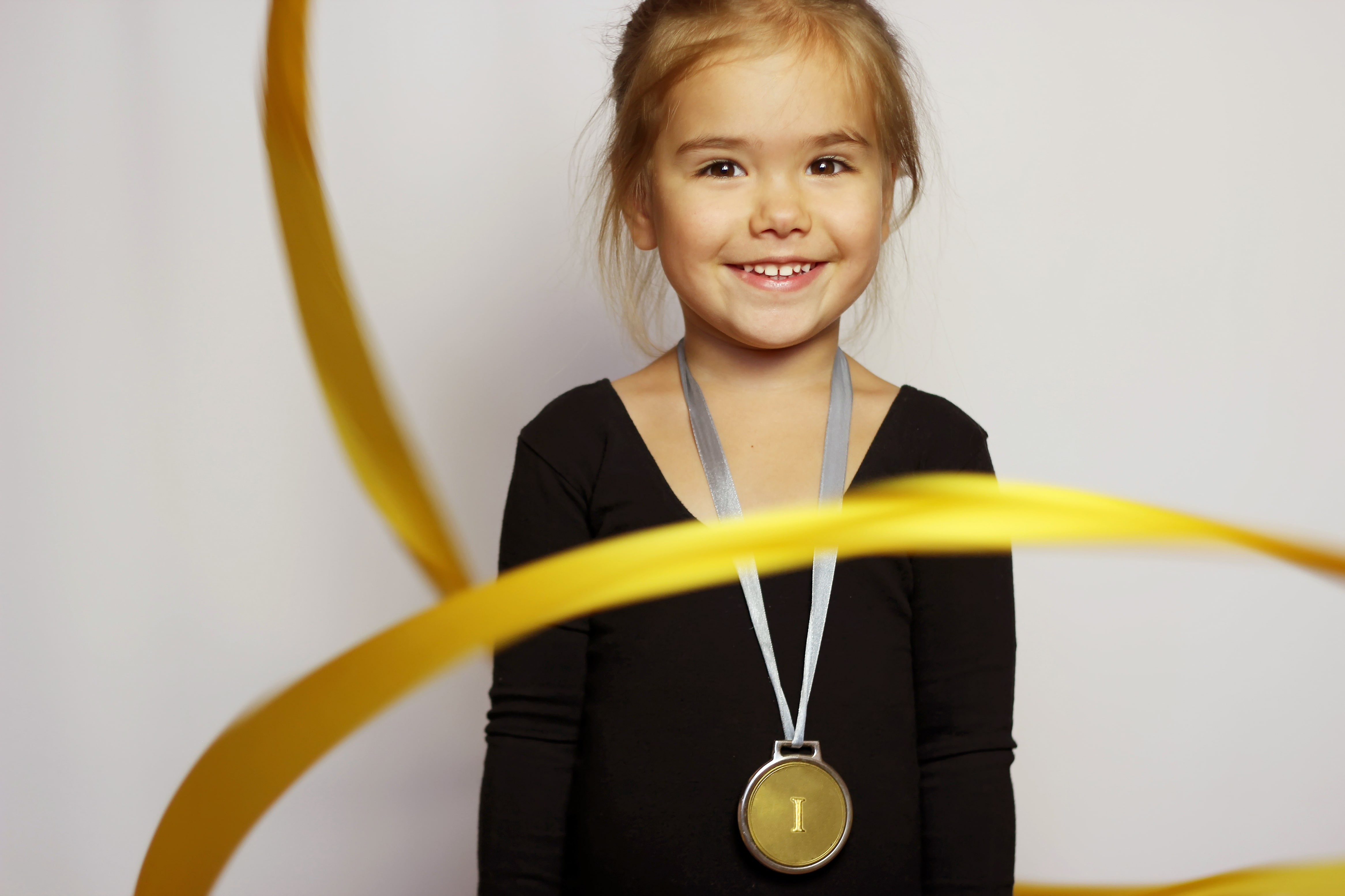 Little girl with gold medal around her neck