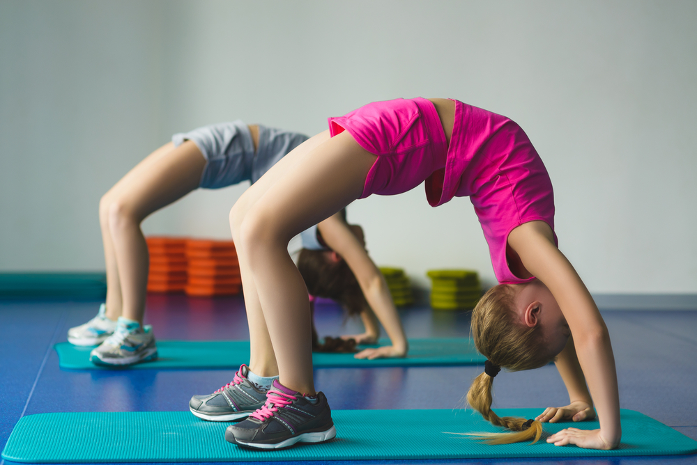Children flexing on gymnastics mats