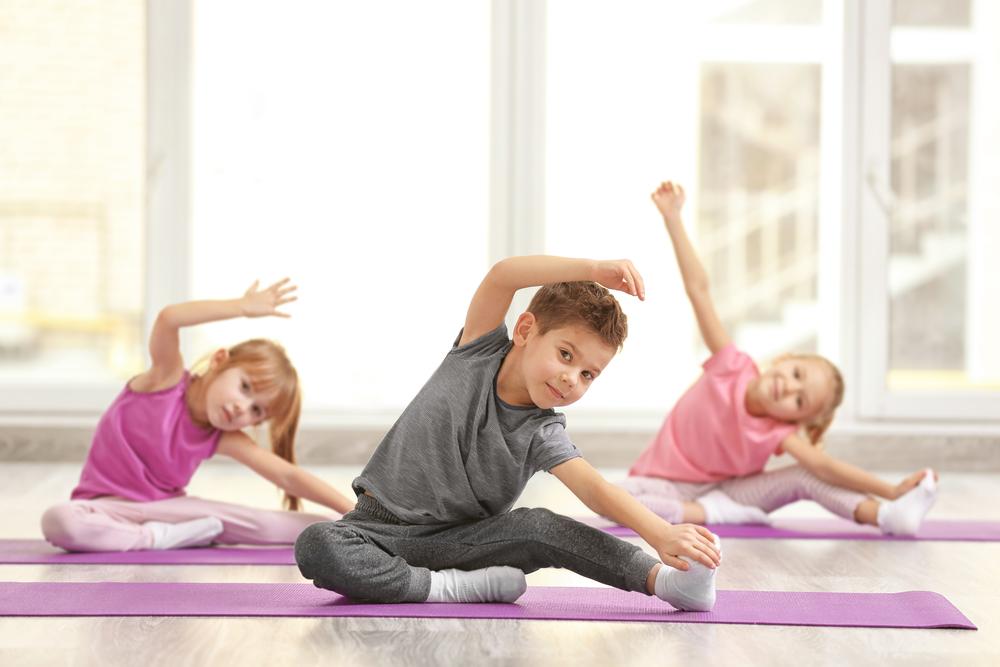Group of children doing gymnastics exercises on mats