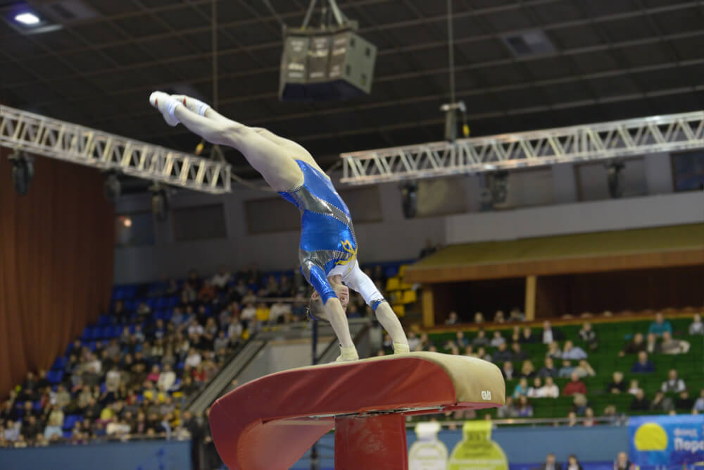 Woman performing stunt on gymnastics vault