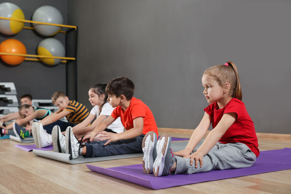 Young children stretching on mats in room