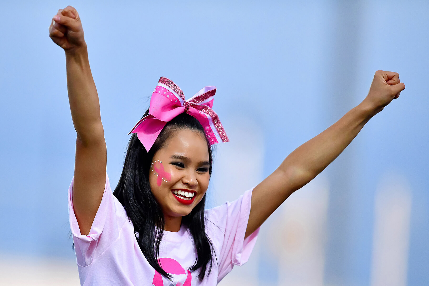 Girl wearing pink ribbon in hair cheering