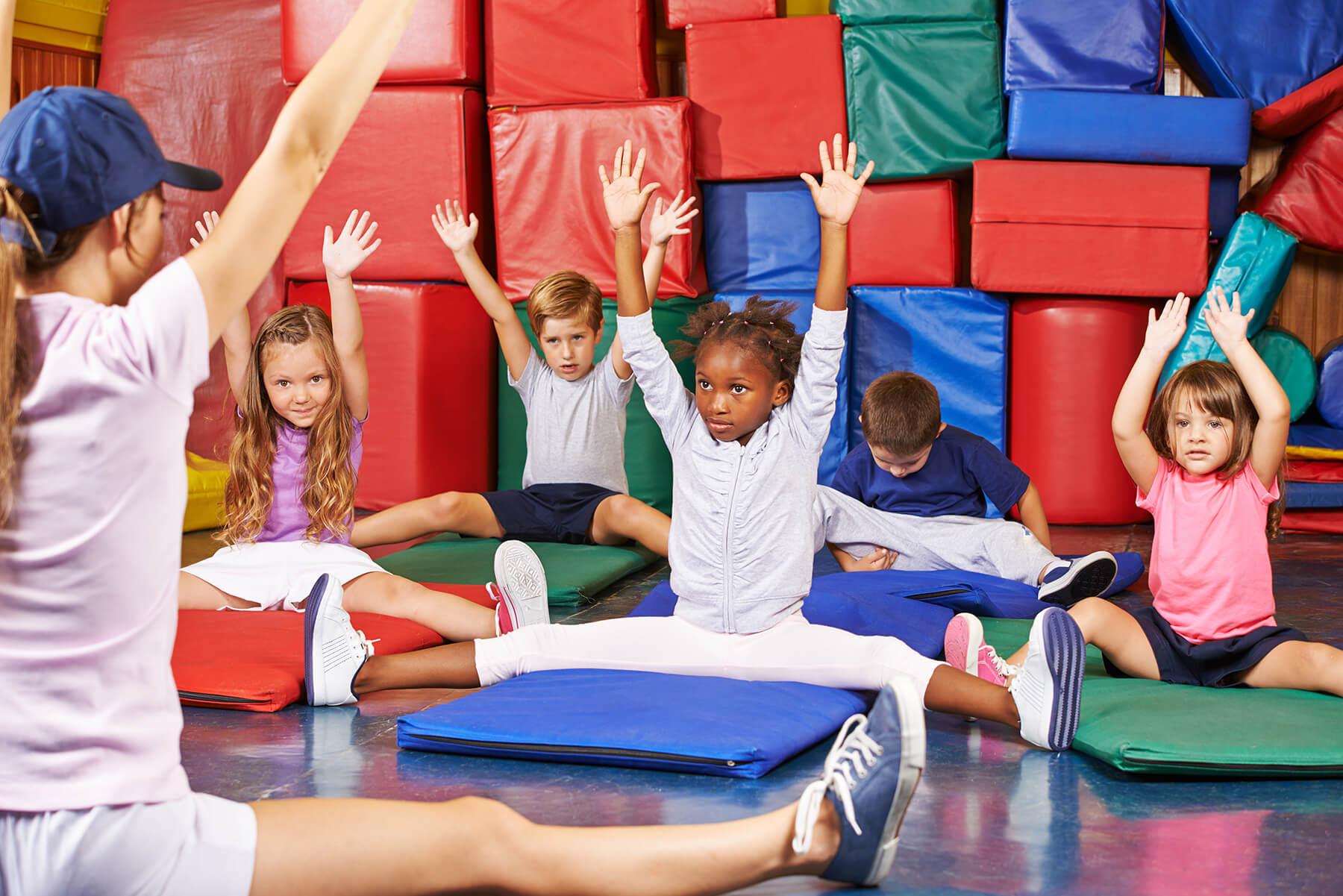 Children taking gymnastics class with instructor teaching