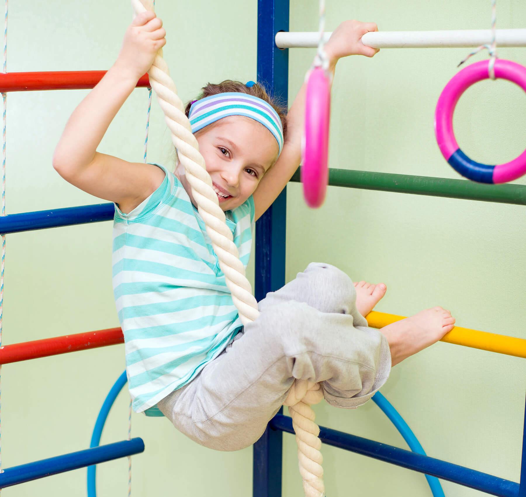 Girl climbing rope in gymnastics class