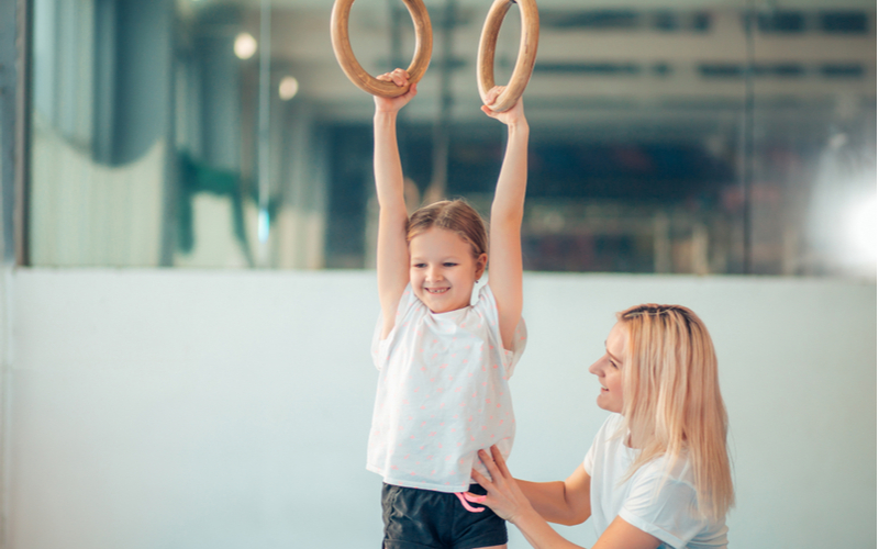 Teacher and little girl working on gymnastics rings